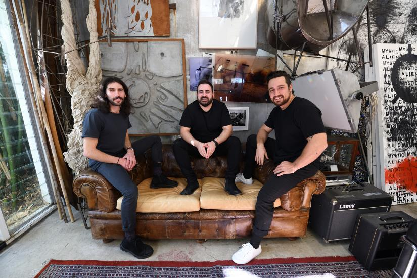 Three UTS Architecture graduates wearing all black sitting on a couch and smiling at the camera