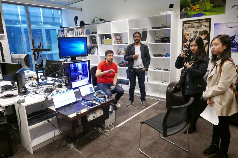 Four people sit and stand in a brightly lit room full of computer screens and gadgets on shelves, and look to the left of the camera