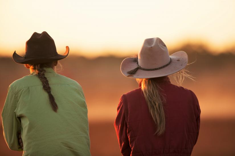 two girls in hats watch an outback sunset