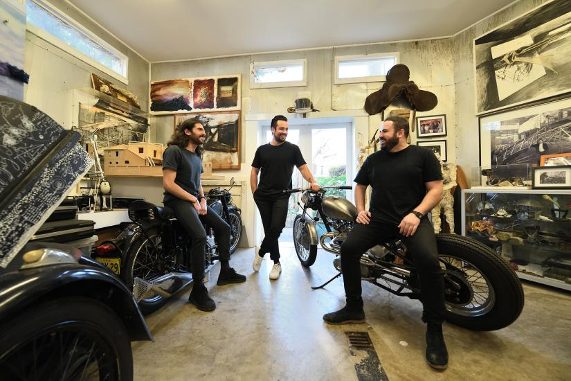 Three UTS Architecture graduates lean on motorcycles and smile at one another