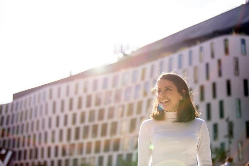 Smiling female lit by sunlight in front of UTS building 7