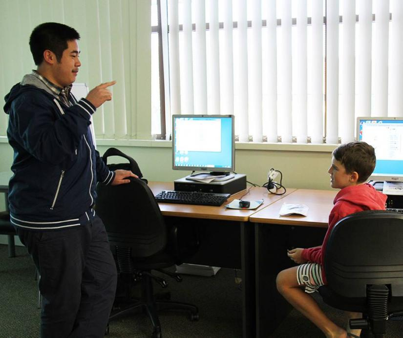 Chau Au talking to a student at Code Club