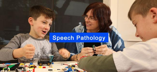 Female speech pathologist working with two male children patients playing lego.