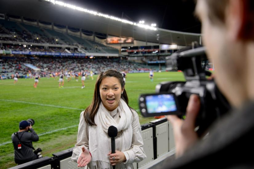 Sports Media student reporting on the field of a live football game