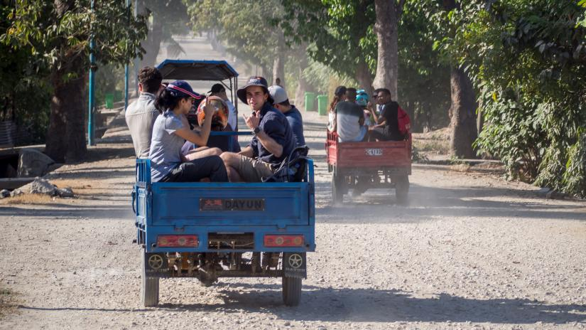 Students in the back of a motorcycle trailer in Timor-Leste