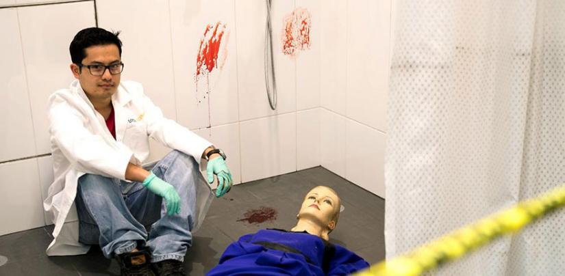 Man sitting in shower next to a mannequin. Blood smears on the tiles