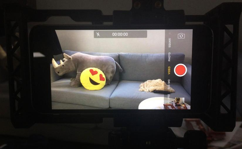 An iPhone filming a couch with cushions on it