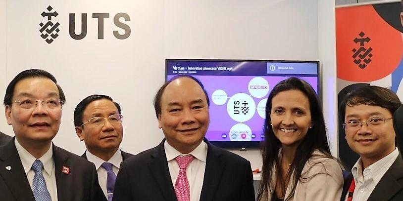A group of people stand smiling in front of a screen and a banner