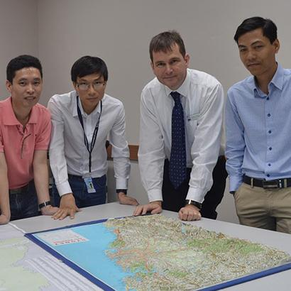 A group of people stand around a map on a table