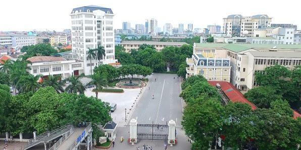 A tree lined avenue sweeps between buildings with the city of Hanoi in the distamce