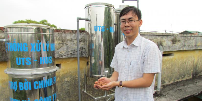 A man stands smiling  next to steel drums with blue text in Vietnamese