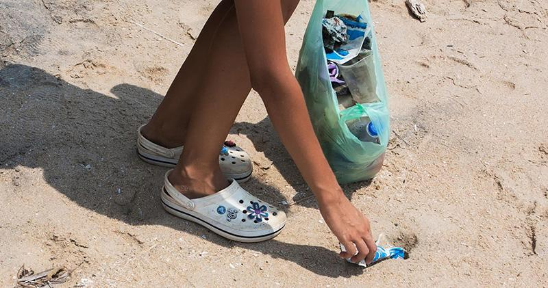 Girl picking up plastic litter, Goa, India
