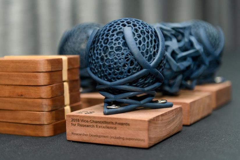Photo of 3D-printed globe-shaped research award statuettes, , designed by Professor Jennifer Loy, School of Design. Photo: Encapture Photography.