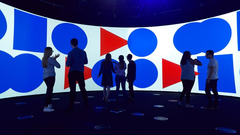 Photo of people assembled in front of a huge screen in the UTS Data Arena