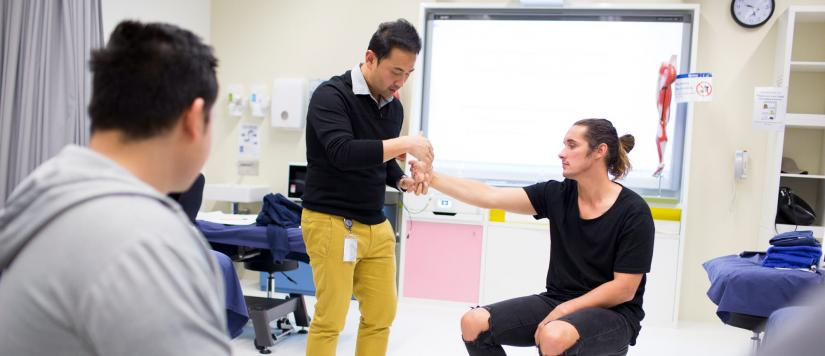 Male physiotherapist treating male client in classroom with male student watching.