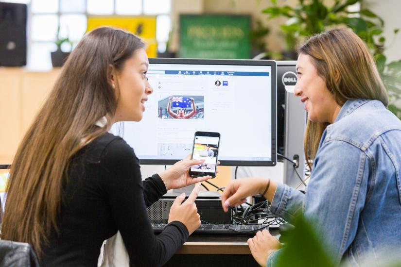 Two women discussing app displayed on iphone infront of two computer screens whilst sitting down