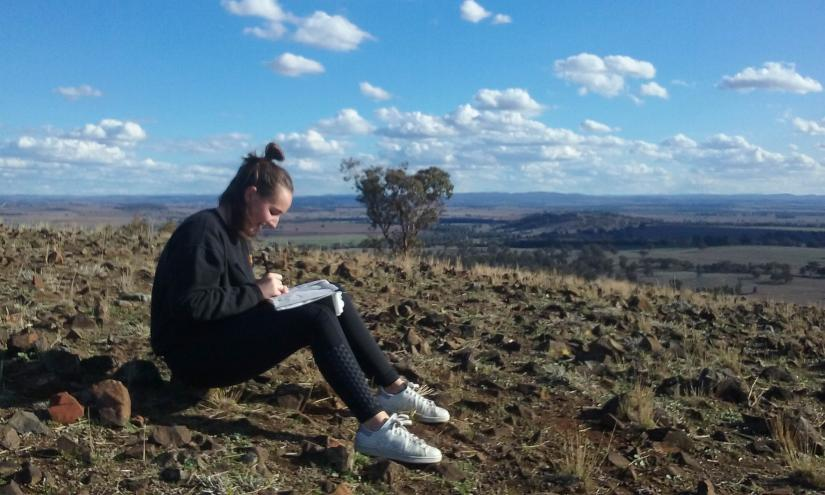 UTS Interior Architecture student sits drawing in regional landscape