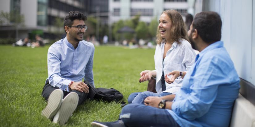 Three students sitting on Alumni Green talking with each other and smiling