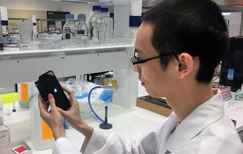 Hao He holding his mobile phone cancer test prototype