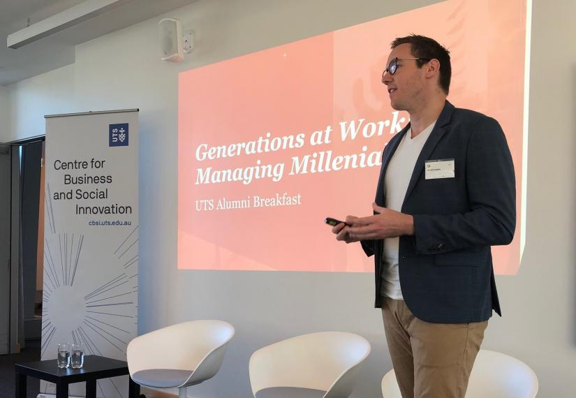 Ben Hamer in front of screen that says 'Generations at Work: Managing Millenials'
