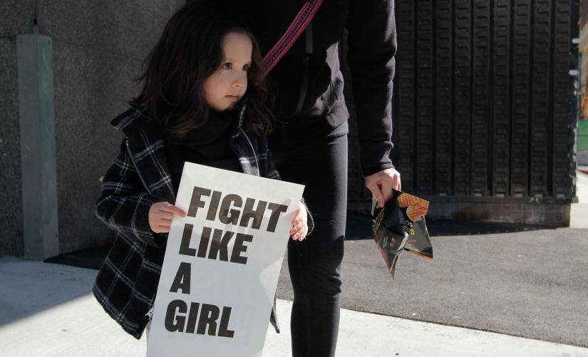 A young girl holds a sign that reads 'fight like a girl'