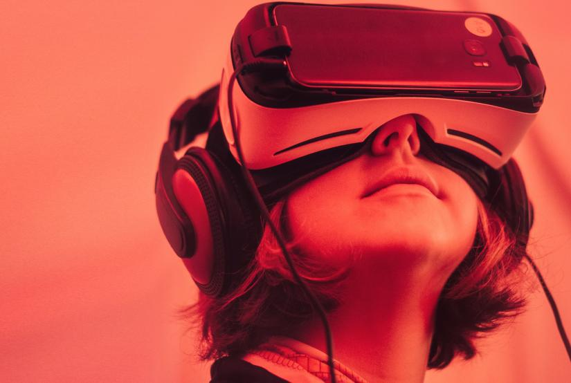 Close up image of a young woman's face, wearing a VR headset and gazing upwards