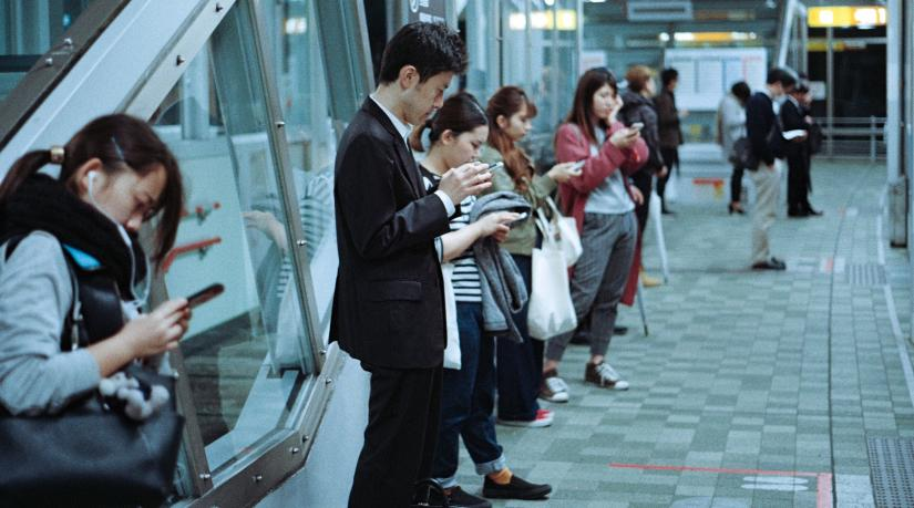 A group of people stand at a train station, all looking down at their mobile phones