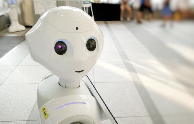 A robot, with a cute appearance looks over its shoulder at the viewer. It is in a public place with an indistinct background