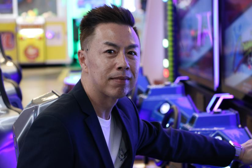 Man with black hair standing in front of a car racing game in a games arcade. Photo by Fiona Livy.