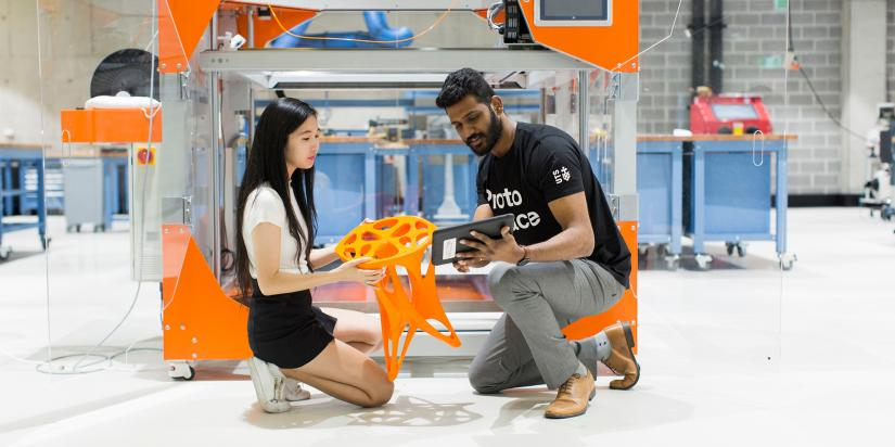 Two students inspect a 3D printed stool