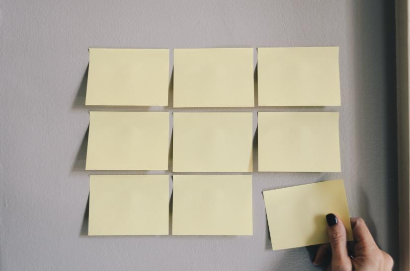 A female hand removes a yellow Post-it note from a grid of nine on a wall