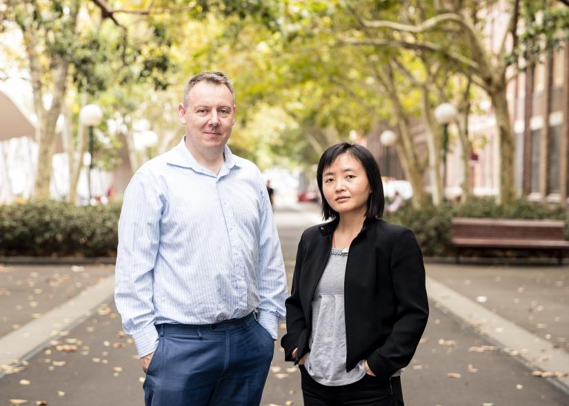Brian Oliver and Hui Chen stand in front of trees, looking at the camera.