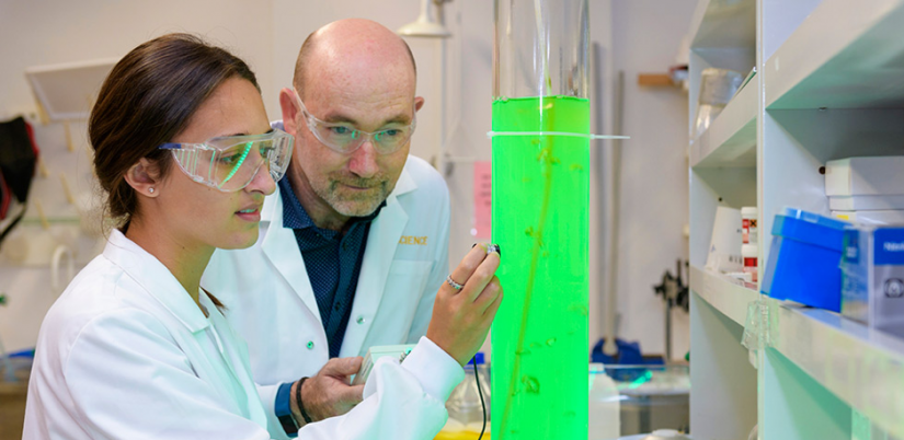 Peter Ralph and a student work in a lab with brightly lit algae