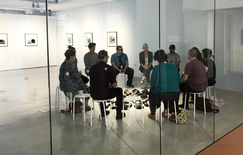 A group of people sit talking. They are seated on stools in a circle around an artwork made of black stones.