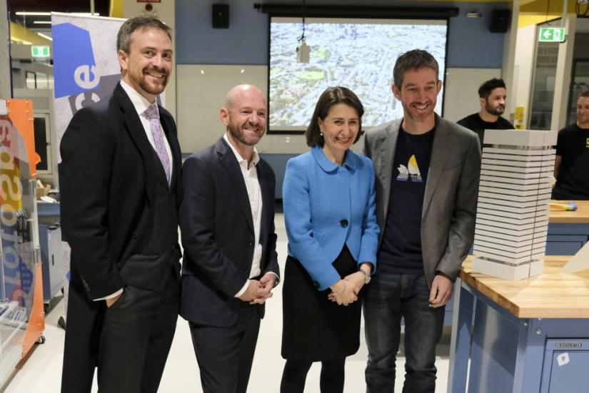 Professor Attila Brungs, Minister Niall Blair, Premier Gladys Berejiklian and Atlassian's Scott Farquhar stand smiling. A model of the UTS tower is in the foreground.