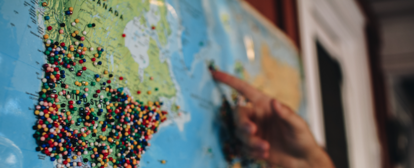 Map of the world with lots of pins in it and a hand pointing to some of the pins