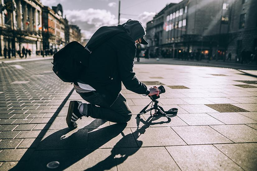 Person setting up a camera on the street. Photo by Stephen Kennedy via unsplash.com
