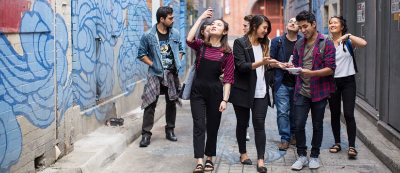 Students walking down an alleyway taking photos and notes