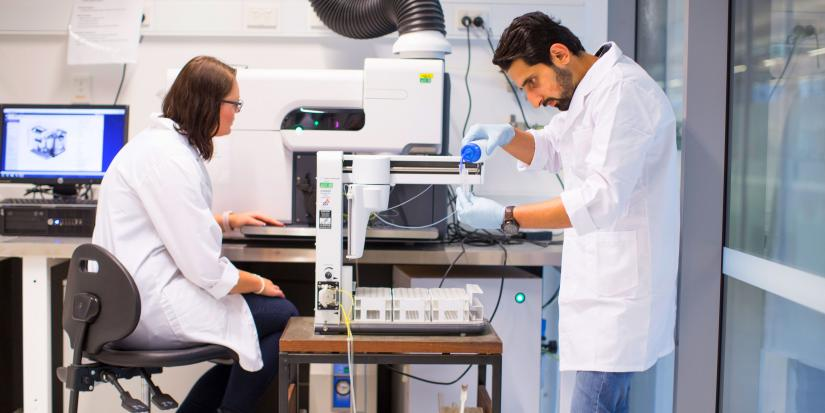 A female and a male researcher working together inside a lab