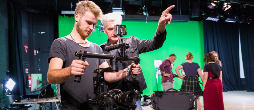 A student holding a camera gimbal, with a green screen in the background
