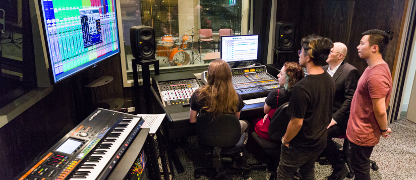 A group of students recording music in a sound booth