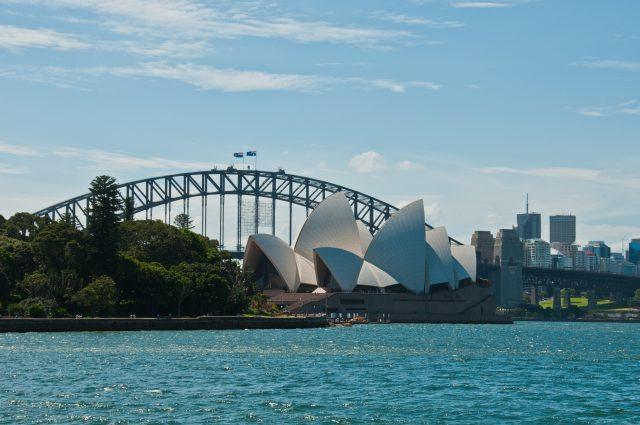 Sydney harbor bridge with the Sydney opera house in front on the harbor