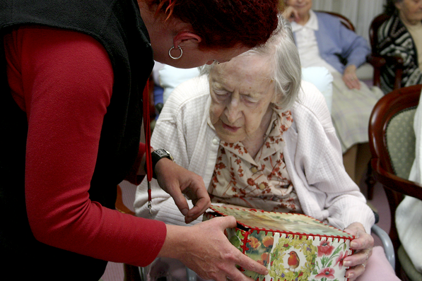 Elderly woman holding museum-in-a-box