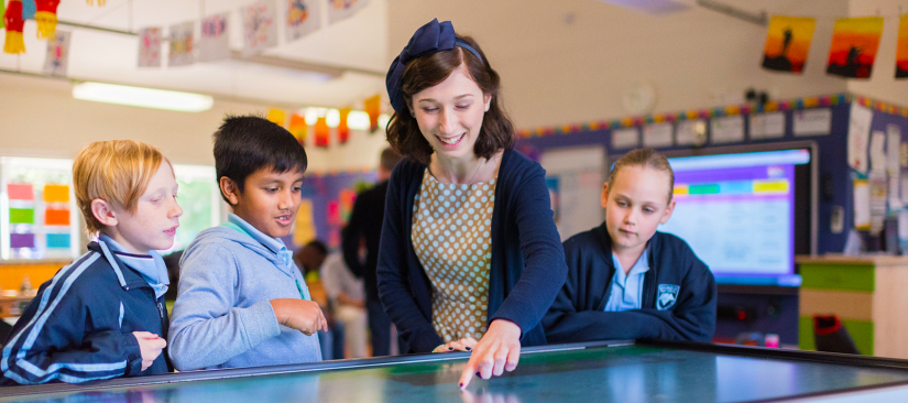 A student teacher points to an interactive board as primary students look on
