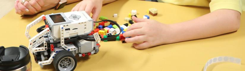 Lego Mindstorm robot and child's hands