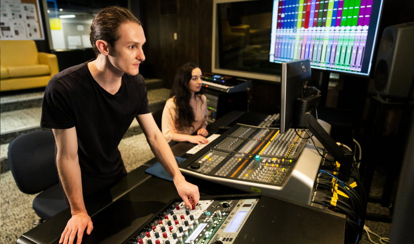 Two students in a sound recording studio, adjusting audio levels on a mixer