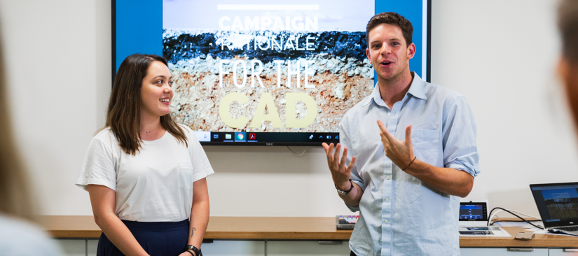 Two students pitching in front of a presentation
