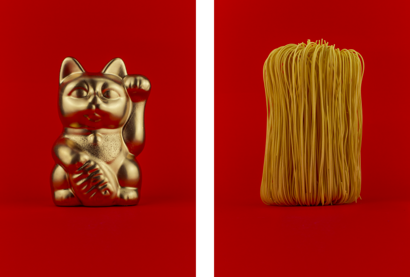 Left: gold waving cat figurine, Right: Dried noodles, both on red background