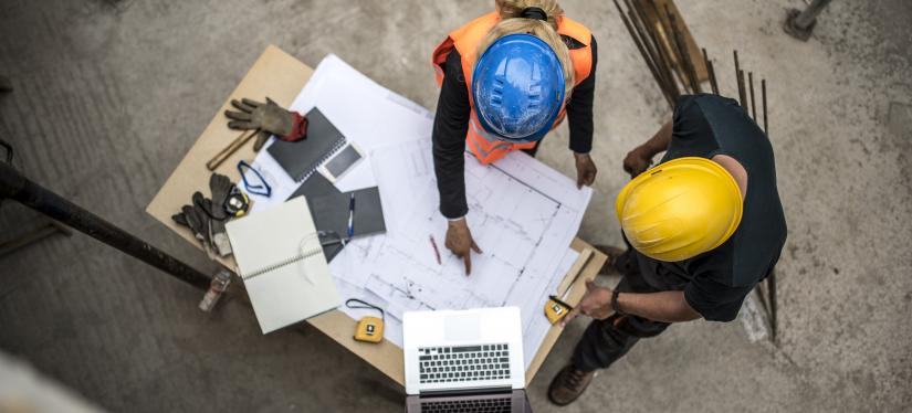 Two colleagues discuss blueprints at a worksite