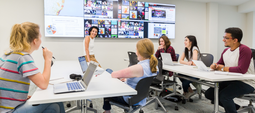 Students sitting in a classroom with news displayed on screens behind